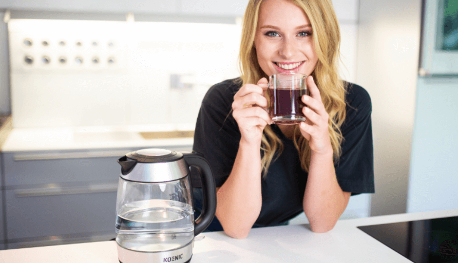 A young, blonde woman drinking tea from a mug, next to a KOENIC kettle, in a modern kitchen